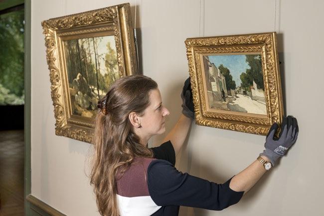 La conservatrice Maite van Dijk règle les derniers détails de l'exposition Des Néerlandais à Barbizon. Maris, Mauve, Weissenbruch devant le tableau Paysage boisé près de Barbizon