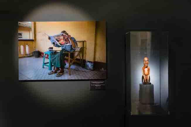 Photographie de Steve McCurry montrant un homme lisant le journal dans une maison pour personnes âgées à Mingun, au Myannmar, 2017, associée à une statuette moai miro de l'île de Pâques conservée au musée Barbier-Mueller. Photo Luis Lourenço.