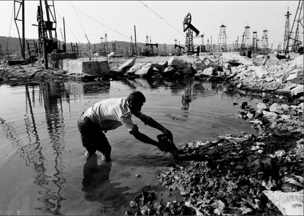 Un pêcheur nettoie une zone pour recycler des déchets dans les anciens champs pétrolifères appartenant à la famille Nobel à Bakou, Azerbaïdjan, 1997 © Stanley Greene /NOOR